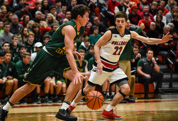 Floyd Central forward Luke Gohmann carries the ball up the court as New Albany guard Isaac Hibbard follows along during the Bulldogs' 65-42 win over the Highlanders on Friday. Staff photo by Tyler Stewart
