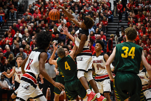 New Albany forward Julien Hunter blocks the shot by Floyd Central guard Matt Weimer during the Bulldogs' 65-42 win over the Highlanders on Friday. Staff photo by Tyler Stewart