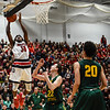 New Albany forward Julien Hunter tries to wrangle in the alley-oop pass from a teammate over Floyd Central's Brendon Hobson during the Bulldogs' 65-42 win over the Highlanders on Friday. Staff photo by Tyler Stewart