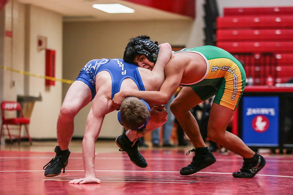 Charlestown's Austin Cooper and FLoyd Central's Wyatt Romines square off during the Wrestling Sectional at Johnson Arena on Saturday. Staff Photo By Josh Hicks