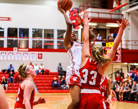 Jeffersonville's Jaylynn Brown collides with Bedford North Lawrence as she lays one up during their game at Johnson Arena on Saturday. Staff Photo By Josh Hicks