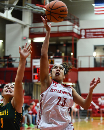 Jeffersonville forward Nan Garcia goes in for a layup past Floyd Central defender Savannah Bartel during the Red Devils' 35-24 win over the Highlanders on Thursday. Staff photo by Tyler Stewart