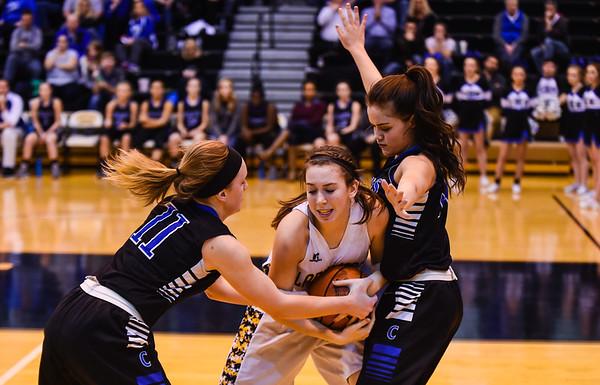 Charlestown's Karston Watson (11) and Jacqueline Biscardi (14) trap Salem's Mariah Mead to gain possession during the Pirates' 55-51 win over the Lions in the Class 3A Corydon Sectional on Wednesday. Staff photo by Tyler Stewart