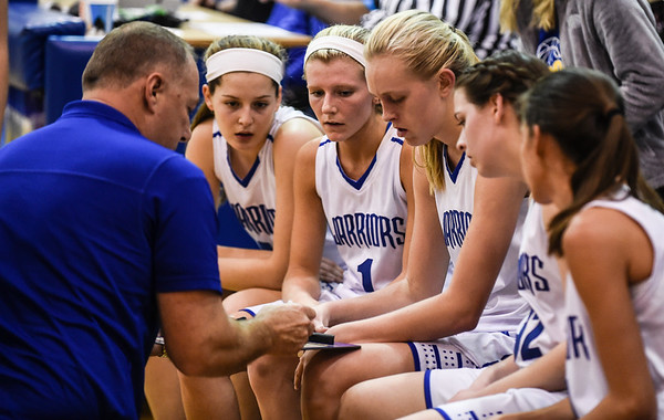 The Warriors use a timeout to review a play with head coach Mike Baird during the Warriors' 48-46 loss to Lanesville on Thursday. Staff photo by Tyler Stewart