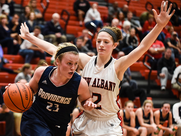 Providence forward Claire Rauck takes the ball past New Albany defender Julyen Condra during the Pioneers' 61-50 loss to the Bulldogs on Friday. Staff photo by Tyler Stewart