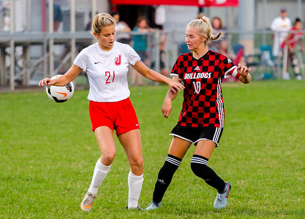 New Albany's Laney Logan Barber sneaks the ball behind Jeffersonville's Blake Schremp during the Bulldogs' game against the Red Devils at Jeffersonvile on Thursday.