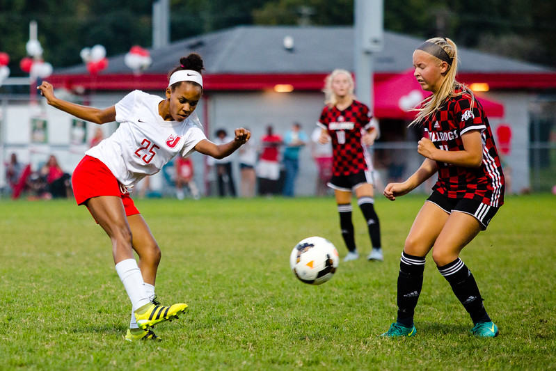 Jeffersonville's Olivia Jones lobs the ball passed New Albany's Grace Barber during the Red Devils' game against the Bulldogs at Jeffersonvile on Thursday.