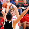 John P. Cleary |  The Herald Bulletin<br /> Knightstown's Jose Olivo gets a hand on the ball as Frankton's Brayton Cain attempts a shot. Olivo was called for a foul on the play.