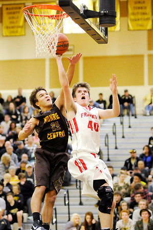 Don Knight | The Herald Bulletin<br /> Frankton's Rylan Detling drives for a layup as he is guarded by Monroe Central's Nick Mitchell in the first round of the sectional at Lapel on Tuesday.