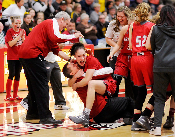 Don Knight | The Herald Bulletin<br /> Destyne Knight knocks her coach Stephen Hamaker down as she jumps in his arms after Frankton beat Monroe Central to win the sectional championship on Saturday.