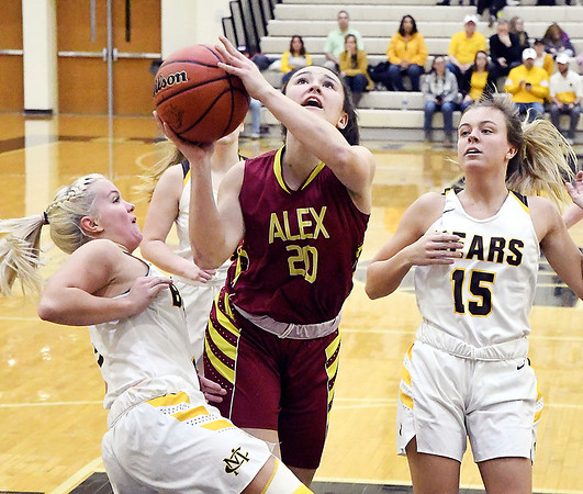 Alexandria's Reiley Hiser goes up for a shot as she gets fouled while driving the lane between Monroe Central defenders.