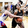 Elwood's Riley Sullivan reaches in for the ball but also fouls Lapel's Morgan Knepp as she drives the lane to the basket.