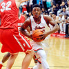 John P. Cleary    The Herald Bulletin<br /> Anderson's Keyounis Woods drives under the outstretched arm of Fishers Connor Washburn as he goes to the basket.