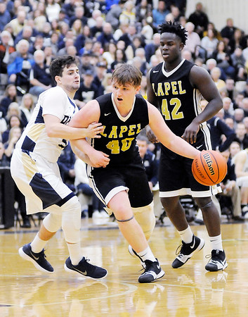 Don Knight | The Herald Bulletin<br /> Lapel's Caleb Bloom drives as he is guarded by Oak Hill's Cal Mann in the first round of the regional on Saturday.