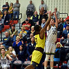 Shenandoah's Evan Coers shoots the three over Howe defender Jalen Stamps during the fourth quarter in the IHSAA 2A Boys Basketball Sectional 42 final at Knightstown on Saturday. Shenandoah defeated Indianapolis Howe 66-50 to win the championship. Richard Sitler photo