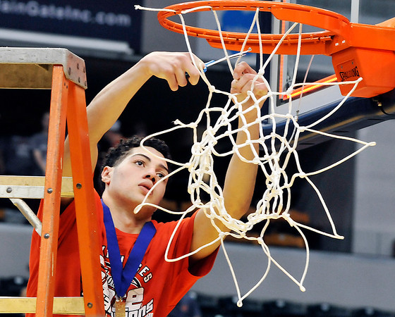 John P. Cleary |  The Herald Bulletin<br /> Frankton's Maurice Knight cuts down the net after the team won the 2A state championship.