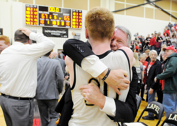 Don Knight | The Herald Bulletin<br /> Lapel coach Jimmie Howell hugs senior Austin Lyons as the Bulldogs celebrate their sectional championship after beating the Frankton Eagles 67-65 on Saturday.