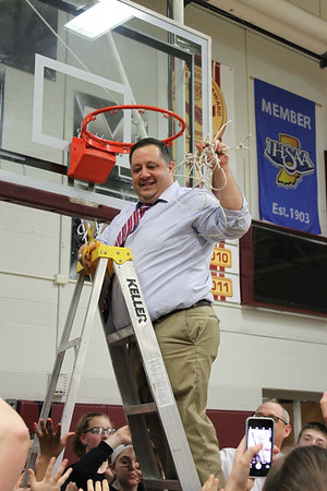 Chris Martin for The Herald Bulletin.  Liberty Christian head coach Jason Chappel  cuts down the net Saturday night at Wes-Del.  Liberty Christian defeated Wes-Del to win the Class 1A Sectioanl 55 Championship.
