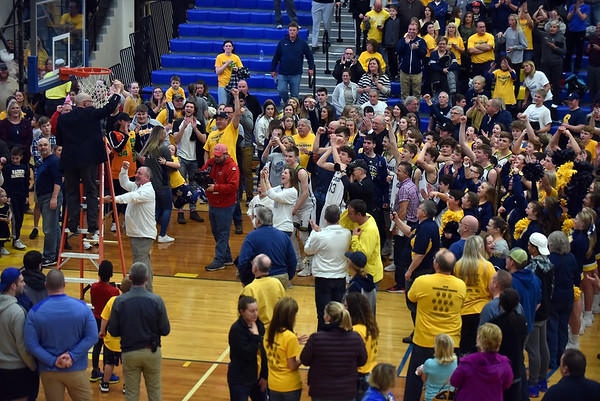 Coach David Bennett cuts down the nets.  Shenandoah defeated Northeastern 42-37 to win the regional championship at Greenfield on Saturday.