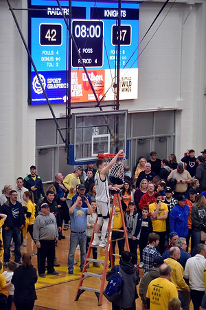 Shenandoah senior Evan Coers takes his turn cutting down the net.  Shenandoah defeated Northeastern 42-37 to win the regional championship at Greenfield on Saturday.