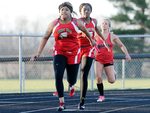 Don Knight | The Herald Bulletin<br /> Desiree King takes the baton from MaKyra Dixon as Anderson wins the 400 relay during the Madison County Track Tournament at Madison-Grant on Friday. Also running legs were Zaharia Howard and Staisha Hamilton.
