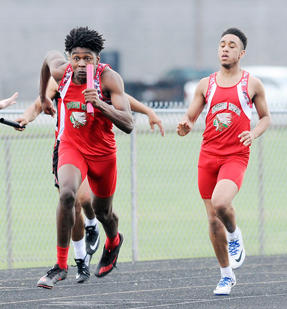 Don Knight | The Herald Bulletin<br /> Anderson's Johnathon Hidleburg gets the baton from Avery Malone as the Indians win the 4x100 relay during the Pendleton Heights Boys Track Invitational on Thursday.