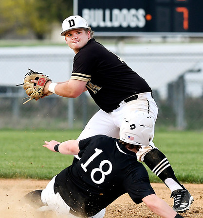 John P. Cleary | The Herald Bulletin <br /> Lapel's #18, Noah Clark slides into second base hard trying to avoid a double play as Daleville shortstop Peyton Smith turns to throw to first but looses the ball out of his mitt to only get the force at second in third inning action.