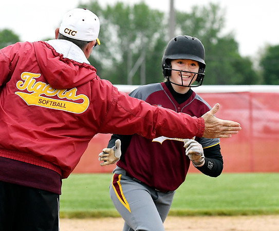 John P. Cleary | The Herald Bulletin <br /> Alexandria's Mackenzie Swango has a big smile on her face as she is congratulated by assistant coach Jimmy King when rounded third base after hitting a a two-run homer in the third inning.