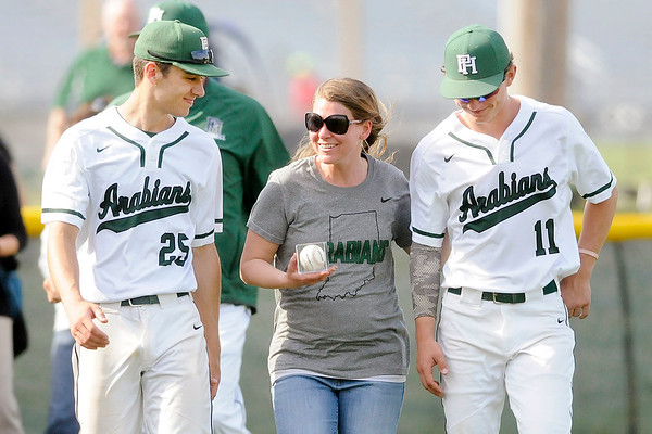 Don Knight | The Herald Bulletin<br /> Pendleton Heights math teacher Anne Plovick joins baseball players Hunter Thompson (25) and Evan Douglas (11) onto the field as the Arabians players recognized the teachers that have influenced them the most during Teacher Appreciation Week on Wednesday.