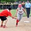 """Frankton's Makena Alexander gets a """"low five"""" from Frankton head coach Jeremy Parker as she heads for home after blasting a grand-slam homerun in the sixth inning to take the lead in the ballgame."""