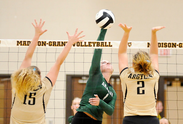 Don Knight | The Herald Bulletin<br /> Pendleton Heights Brynn Teague attacks the ball as Madison-Grant's McKenna Lugar and Morgan Conliff attempt to block her on Thursday.