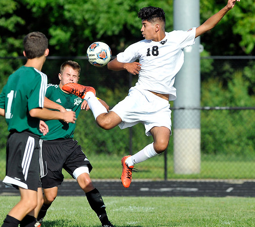 John P. Cleary | The Herald Bulletin<br /> Anderson's Alan Olguin jumps high to kick the ball against Yorktown defenders Garrett Amburn and Michael Bade.
