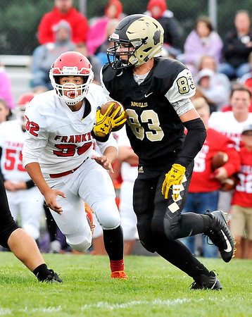 John P. Cleary |  The Herald Bulletin<br />  Madison-Grant's Alex Webb looks up field as Frankton's Will Harris closes in.