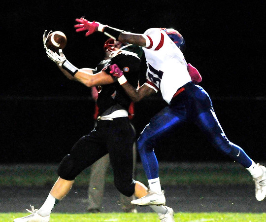 John P. Cleary | The Herald Bulletin<br /> Anderson's Eli Erny, Sr. hauls in a pass from Dylan Barron as Kokomo defender Keenen Wheler tries to tip the ball. The play went for a 41 yard touchdown for the Indians.