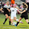 John P. Cleary |  The Herald Bulletin<br /> Pendleton Heights Taylor Fort, #10, splits Mount Vernon defenders Alaina Nelson and Shay Stindle to get a kick off toward the goal.