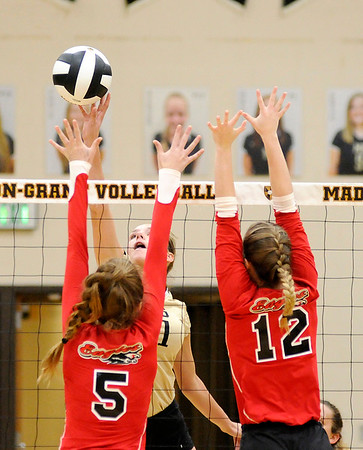 Don Knight | The Herald Bulletin<br /> Madison-Grant's Sloane Stewart tips the ball over Frankton's Kate Sperry and Gabby Carmack on Tuesday.