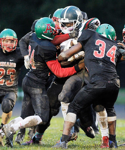 Don Knight | The Herald Bulletin Keyounis Woods, left, and Jaleel Patterson Sr. tackle Arsenal Tech's Gerald Garrett during homecoming on Friday.