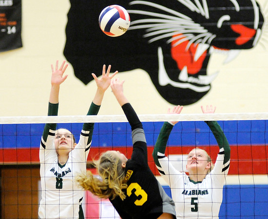 Don Knight | The Herald Bulletin<br /> Pendleton Heights' Averi Lanman and Michelle Merryman attempt to block Alexandria's Megan Miller during the Madison County Volleyball championship at Elwood on Saturday.