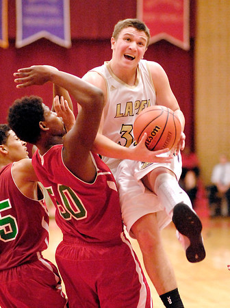 Lapel's Brady Cherry drives through Anderson's Dalton Busch as he goes to the basket for a shot.