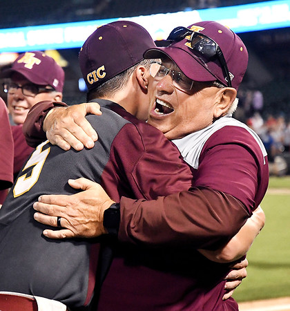 John P. Cleary | The Herald Bulletin<br /> The Alexandria Tigers vs Southridge Raiders in IHSAA 2A Baseball State Championship. Alexandria head coach Jeff Closser gets a big hug from Cade Vernetti after winning the 2A championship.