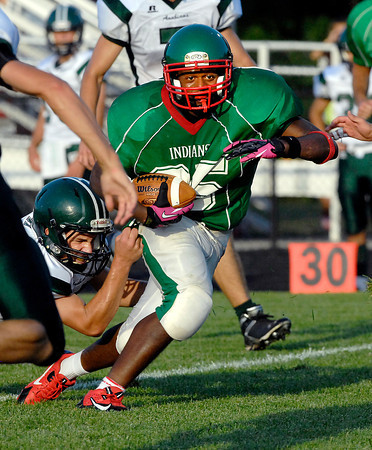 Anderson's running back Tyler Welch breaks the grip of Pendleton's Nathan Grile.
