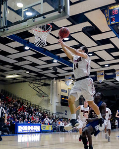 Nicolas Conforti # 14 soars to the basket past a Woodson defender