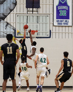 Chris Weaver #24 takes the ball above the rim while South Lakes defender Emmanuel Aghayere #50 defends.