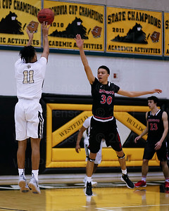 Westfield's Marshall Reed #11 fires a 3 pointer over Herndons Corey Myers #30. Reed led allscorers with 22 points while Myers led Herndon with 14.