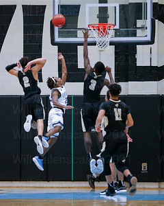 Jordan Hairston #2 and Aaron Opoku #3 both defend a Centreville player