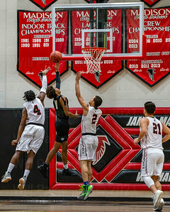Westfield's Tahj Summey #11 takes the ball to the glass between Madison defenders John Finney #4 and AJ Arnolie #2
