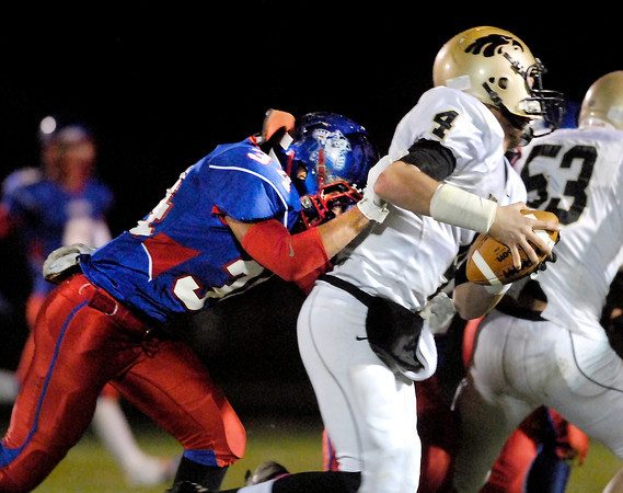 Elwood's Bryce Graves hits Churubusco's quarterback Jay Petrie from behind for a sack.