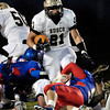 Churubusco's Jason Nicodemus runs over two Elwood defenders.