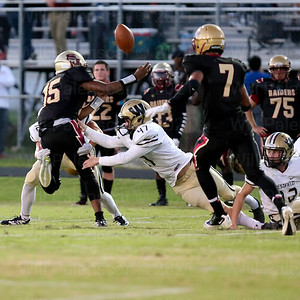 Russell Steinhilber #12 and Alex Shadkoo #47 force a fumble by Stonewall Jackson QB Anthony Jacobs #15.