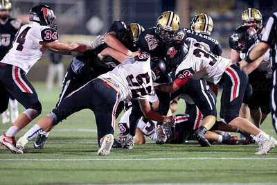 Madison defenders Tommy Williams #32 and Bennett Jackins #52 look to stop Westfield ball carrier Eugene Asante.